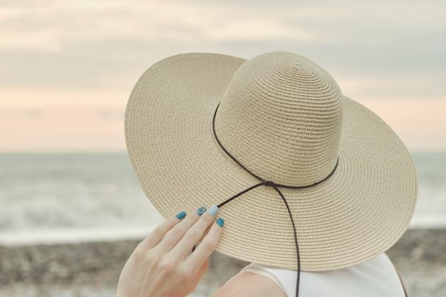 Dziewczyna w kapeluszu siedzi nad morzem. widok z tyłu. zbliżenie