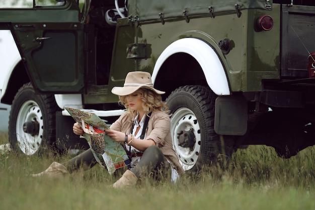 Dziewczyna w kapeluszu siedzi obok samochodu z mapą