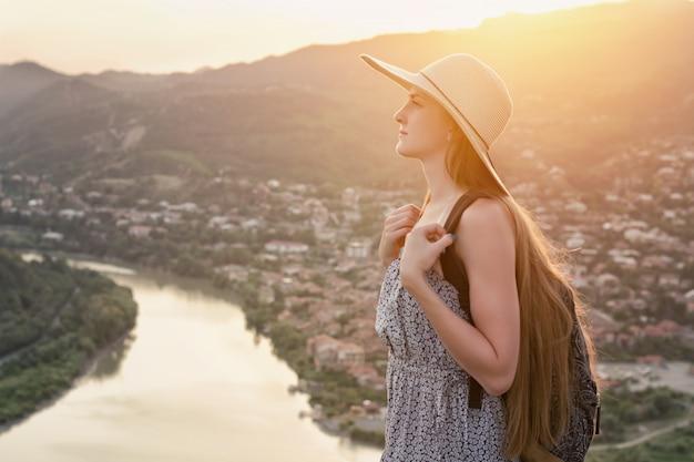 Dziewczyna w kapeluszu stoi na wzgórzu. rzeka i miasto poniżej. zachód słońca