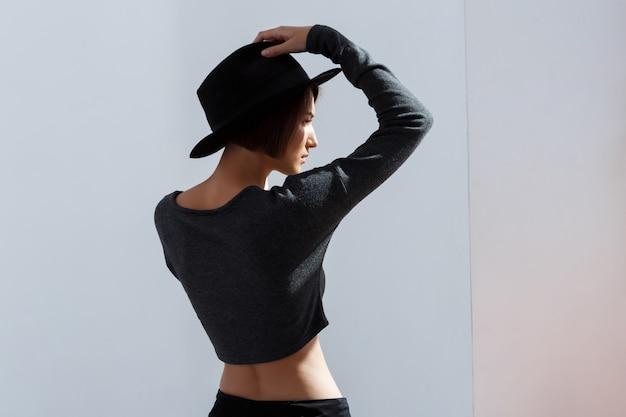 Dziewczyna w kapeluszu stoi z powrotem nad biel ścianą
