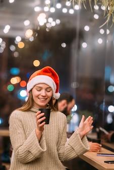Dziewczyna w kapeluszu świętego mikołaja siedzi w kawiarni i pije kawę
