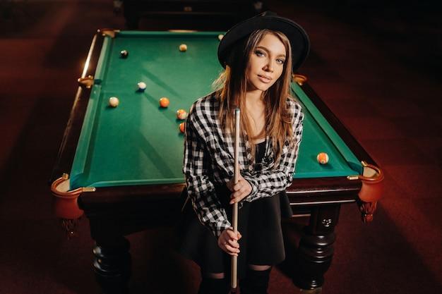 Dziewczyna w kapeluszu w klubie bilardowym z kijem w rękach. gra w bilard.