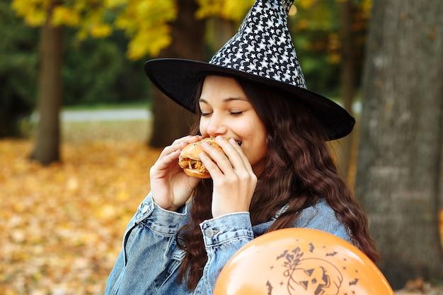 Dziewczyna w kapeluszu wiedźmy obok pomarańczowego balonu na halloween je burgera w jesiennym parku