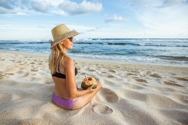 Dziewczyna w kapeluszu z kokosem siedzi na plaży, widok z tyłu