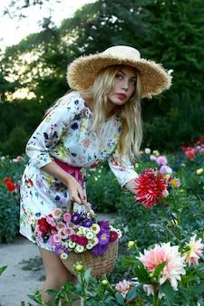 Dziewczyna w kapeluszu z koszem kwiatów w polu dalii