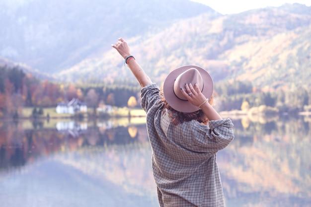 Dziewczyna w kapeluszu z plecakiem stoi nad brzegiem górskiego jeziora