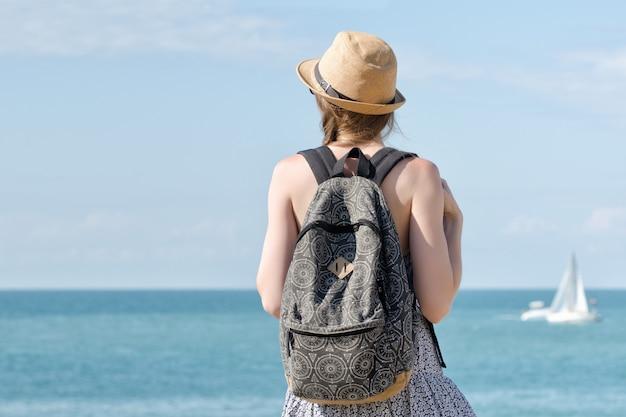 Dziewczyna w kapeluszu z plecakiem stojącym na wybrzeżu. jacht w oddali. widok z tyłu