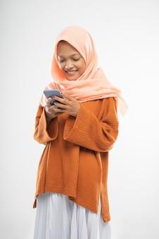Dziewczyna w kapturze stoi trzymając telefon komórkowy