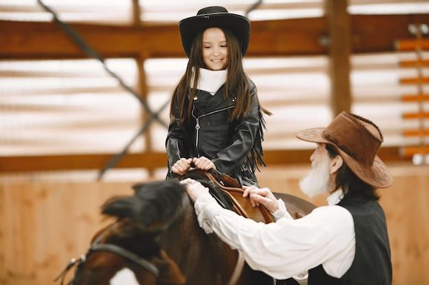 Dziewczyna w kasku nauka jazdy konnej. instruktor uczy małą dziewczynkę.
