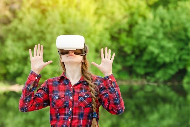 Dziewczyna w kasku rzeczywistości wirtualnej na tle przyrody. ręce do góry
