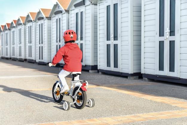 Dziewczyna w kasku uczy się jeździć na czterokołowym rowerze w pobliżu przebieralni