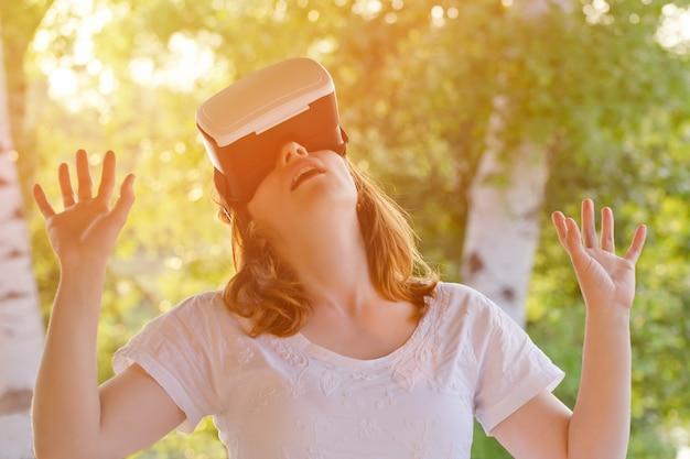 Dziewczyna w kasku wirtualnej rzeczywistości na przyrodę. cud