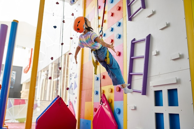Dziewczyna w kasku wisi na linie przy ściance wspinaczkowej, centrum rozrywki, młody wspinacz. dzieci bawiące się, dzieciaki spędzają weekend na placu zabaw, szczęśliwe dzieciństwo