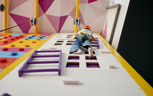 Dziewczyna w kasku wisi na ściance wspinaczkowej, widok z dołu. centrum rozrywki, młody wspinacz. dzieci bawiące się, dzieciaki spędzają weekend na placu zabaw, szczęśliwe dzieciństwo