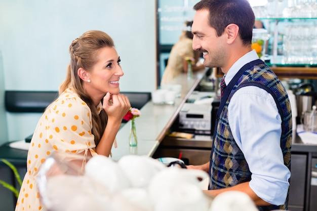 Dziewczyna w kawiarni lub kawiarni flirtuje z barista