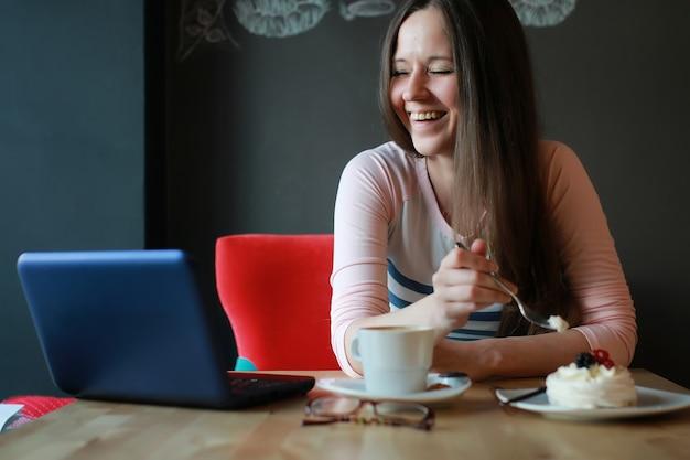 Dziewczyna w kawiarni na filiżankę kawy z notatnikiem