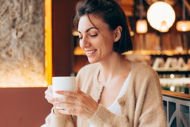 Dziewczyna w kawiarni przy filiżance gorącej kawy latte