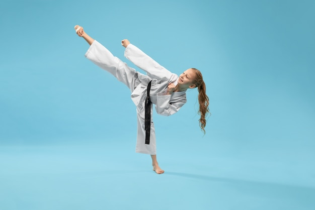 Dziewczyna w kimono ćwiczy kopnięcie stopę do przodu.