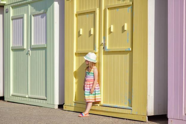 Dziewczyna w kolorowej sukience w pobliżu kolorowych drewnianych domów nad oceanem saint aubin sur mer