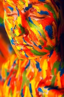 Dziewczyna w kolorowych pociągnięciach farby w studio