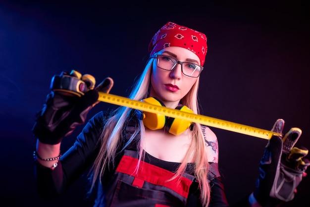 Dziewczyna w kombinezonie budowlanym i słuchawkach w neonowym świetle, robiąca naprawy domu za pomocą taśmy mierniczej