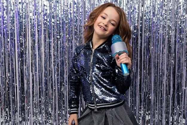 Dziewczyna w konkursie talentów z mikrofonem na błyszczącej ścianie