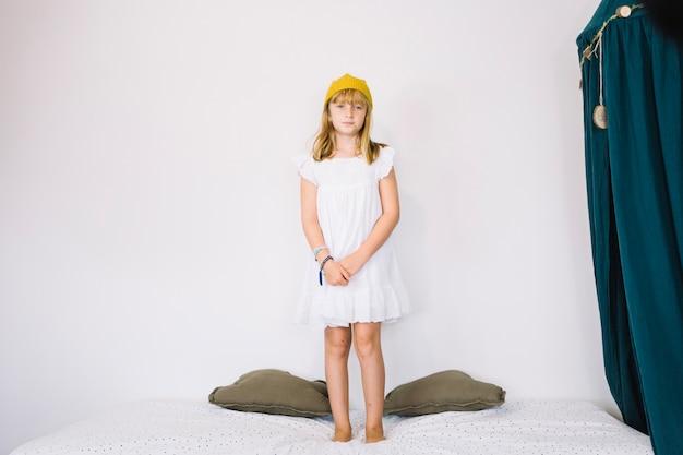 Dziewczyna w koronie stoi na łóżku