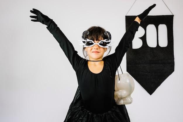 Dziewczyna w kostium halloween gospodarstwa rąk do góry