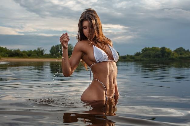 Dziewczyna w kostiumie kąpielowym na brzegu rzeki