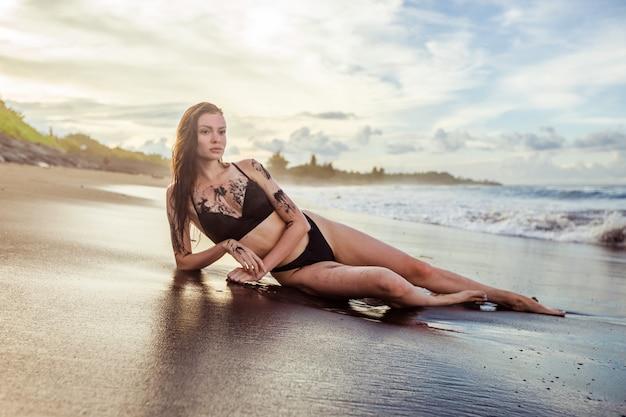 Dziewczyna w kostiumie kąpielowym pokrytym czarnym piaskiem leży na plaży