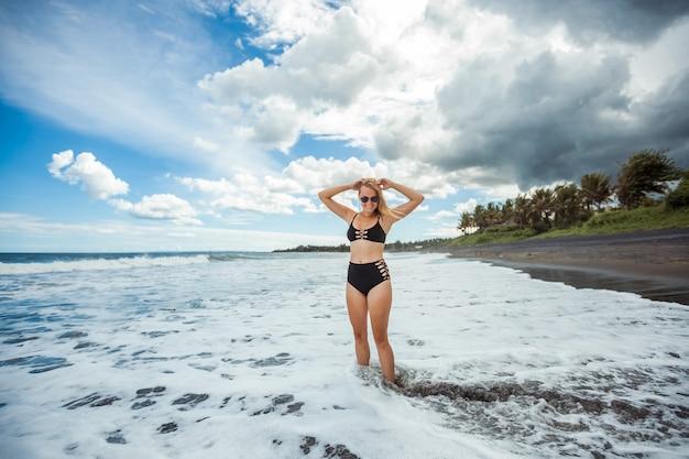 Dziewczyna w kostiumie kąpielowym stojącej na fali morskiej