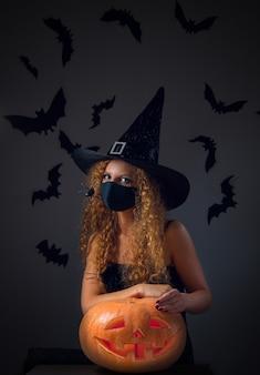 Dziewczyna w kostiumie karnawałowym i masce medycznej trzyma w rękach jack o lantern na halloween