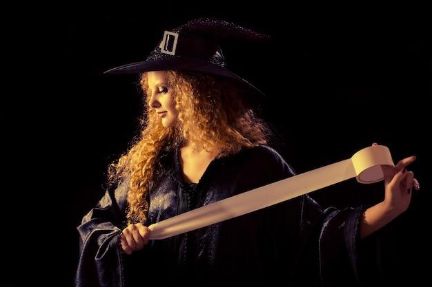 Dziewczyna w kostiumie karnawałowym trzyma taśmę ostrzegawczą na czarnym tle