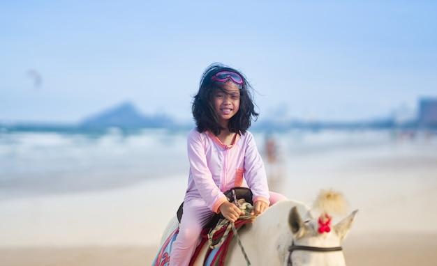 Dziewczyna w kostiumie pływackim jedzie konia na plaży