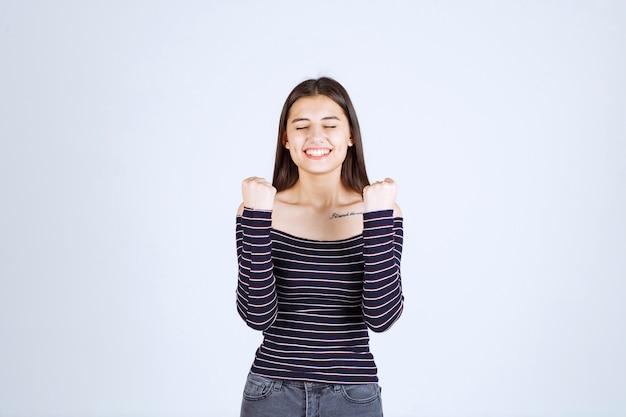 Dziewczyna w koszuli w paski, demonstrując jej mięśnie ramion.