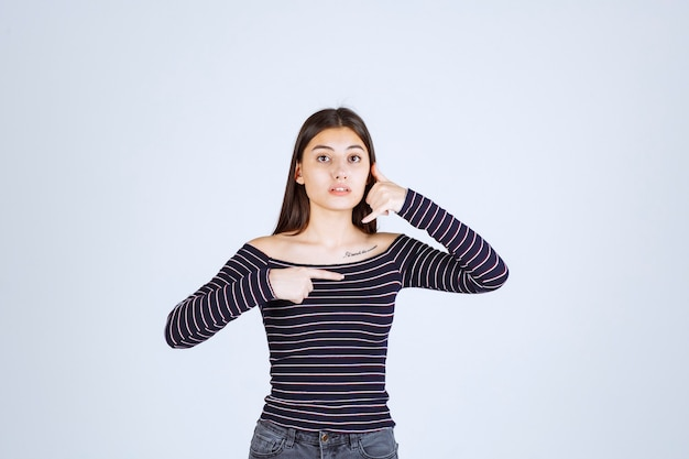 Dziewczyna w koszuli w paski pokazując prawą stronę i prosząc o telefon.