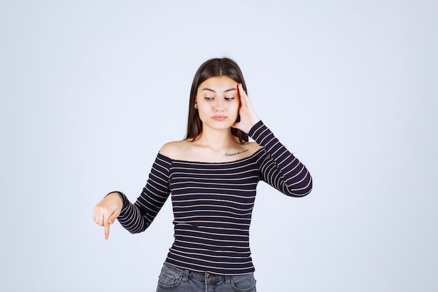 Dziewczyna w koszuli w paski, trzymając głowę, gdy jest wyczerpana lub ma ból głowy.