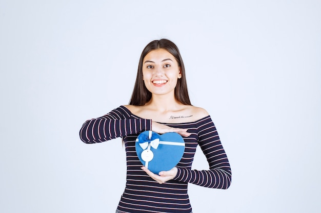 Dziewczyna w koszuli w paski, trzymając niebieskie pudełko w kształcie serca i uśmiechając się.