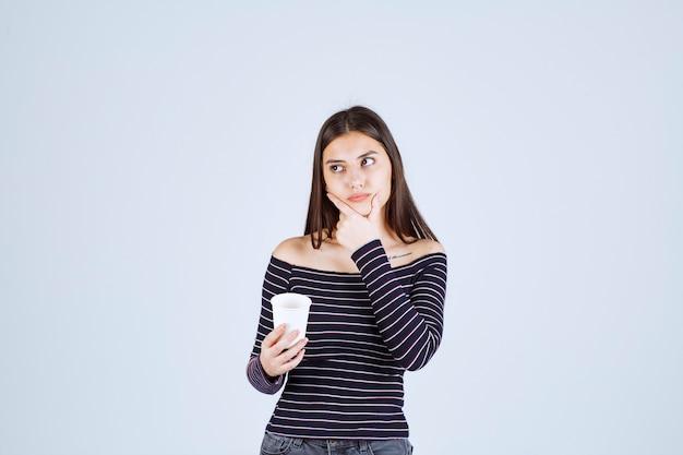 Dziewczyna w koszuli w paski, trzymając plastikowy kubek do kawy i myślenia.