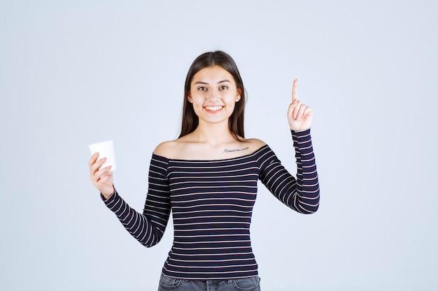 Dziewczyna w koszuli w paski, trzymając plastikowy kubek do kawy i wprowadzając ją jako produkt.