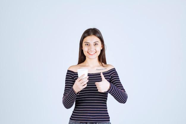 Dziewczyna w koszuli w paski, trzymając plastikowy kubek do kawy i wskazując na dobry smak.