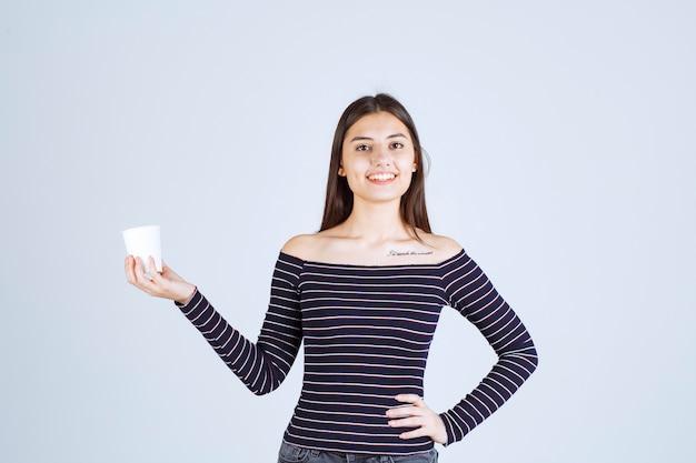 Dziewczyna w koszuli w paski, trzymając plastikowy kubek do kawy i wygląda pozytywnie.