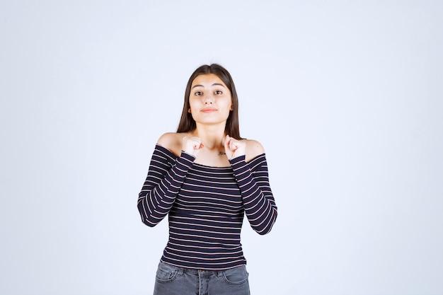 Dziewczyna w koszuli w paski wygląda na zdezorientowaną i podekscytowaną.