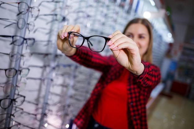 Dziewczyna w koszuli wyciąga i mierzy sobie okulary