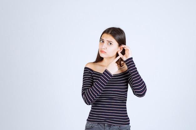 Dziewczyna w koszuli z lamówką, pokazując jej ucho.
