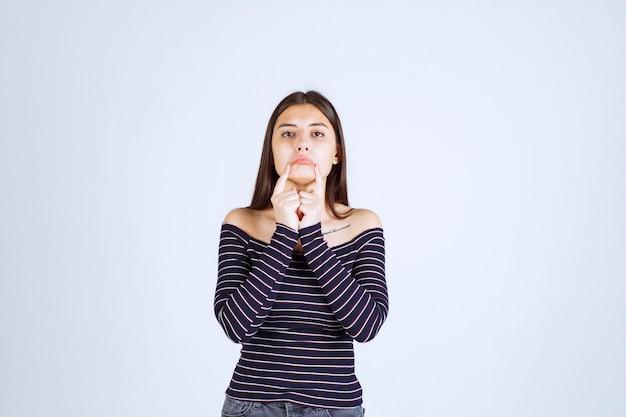 Dziewczyna w koszuli ze szwami wygląda na chorego i pokazuje usta.
