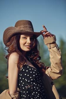 Dziewczyna w kowbojskim kapeluszu, odpoczynek w wiosce w pobliżu stajni, portret kobiety w słońcu, styl rustykalny. portret seksownej brunetki w przyrodzie. idealny makijaż, kosmetyki naturalne