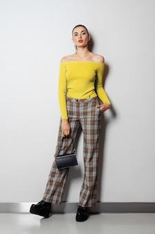 Dziewczyna w kraciaste spodnie i żółty sweter z małą torebką pozowanie w pobliżu białej ścianie