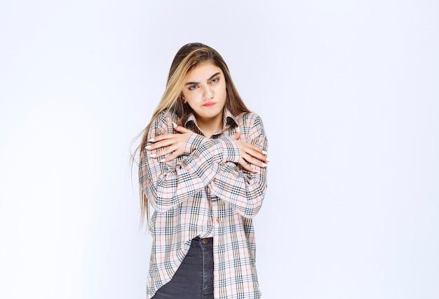 Dziewczyna w kraciastej koszuli krzyżuje ramiona i jest jej zimno