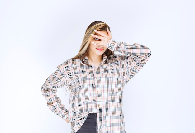 Dziewczyna w kraciastej koszuli patrząca przez palce